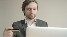 Взгляд бизнесмена на кредитной карточке пока использующ компьтер-книжку на деревянном столе в офисе Вид спереди видеоматериал