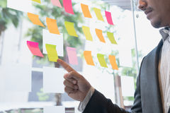 Взгляд бизнесмена на примечаниях прилипателя на стеклянной стене в встрече Стоковые Изображения RF