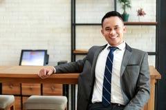 Взгляд бизнесмена ослабляет сидеть и усмехаться на кофейне стоковые изображения rf