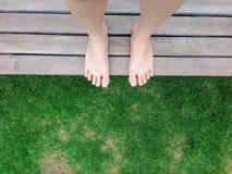 Взгляд босых ног на зеленой траве в саде Стоковые Изображения RF