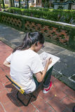Взгляд визирования особняка и сада семьи Lin Бен-юаней, одна девушка сидит на стуле и рисует дерево на бумаге с карандашем Стоковое Изображение RF