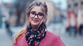 Взгляд вращения красивой маленькой девочки в стильном взгляде, с очаровательным стилем причёсок стоять в центре города и видеоматериал