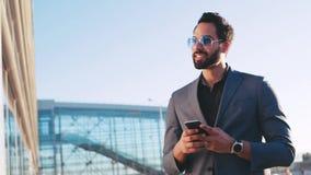 Взгляд вращения привлекательного человека в костюме используя его мобильный телефон и счастливо усмехаться, смотря вокруг, радост сток-видео