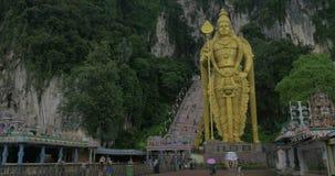 Взгляд входа в пещеры Batu, лестницу и статую золота Murugan против горы, Gombak, Selangor, Малайзии сток-видео