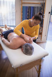 Взгляд высокого угла без рубашки старшего мужского пациента лежащ на кровати получающ массаж шеи от женщины Стоковая Фотография RF