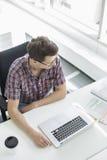 Взгляд высокого угла бизнесмена работая на столе в творческом офисе Стоковая Фотография RF
