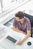 Взгляд высокого угла бизнесмена работая на столе в творческом офисе Стоковые Фотографии RF