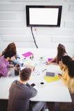 Взгляд высокого угла бизнесменов смотря на телевидении в творческом офисе Стоковое Фото