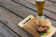Взгляд высокого угла гамбургера на разделочной доске пивом Стоковое Изображение