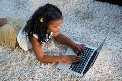 Взгляд высокого угла девушки используя компьтер-книжку Стоковое фото RF