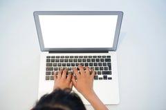 Взгляд высокого угла девушки печатая на компьтер-книжке с пустым экраном Стоковая Фотография