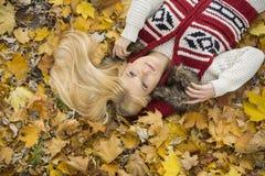 Взгляд высокого угла заботливой молодой женщины лежа на листьях осени в парке Стоковые Фотографии RF