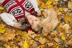 Взгляд высокого угла заботливой молодой женщины лежа на листьях осени в парке Стоковое фото RF