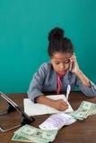 Взгляд высокого угла коммерсантки используя телефон пока пишущ на книге бумажными деньгами Стоковое Изображение