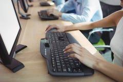 Взгляд высокого угла коммерсантки работая на компьютере в центре телефонного обслуживания Стоковые Фотографии RF