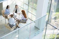 Взгляд высокого угла коммерсанток обсуждая на таблице в офисе Стоковая Фотография RF