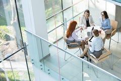Взгляд высокого угла коммерсанток обсуждая на таблице в офисе Стоковая Фотография