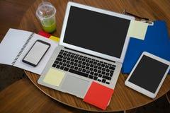 Взгляд высокого угла компьтер-книжки и цифровой таблетки на таблице в офисе Стоковое Изображение RF