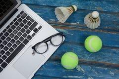 Взгляд высокого угла компьтер-книжки и eyeglasses с shuttlecocks теннисными мячами Стоковое Фото