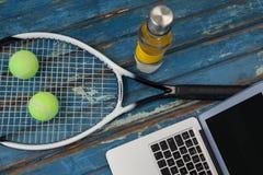 Взгляд высокого угла компьтер-книжки ракеткой тенниса и шариков с бутылкой с водой Стоковые Изображения