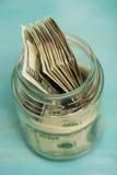 Взгляд высокого угла конца-вверх банкнот доллара в стеклянном опарнике Стоковые Изображения RF