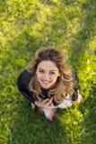 Взгляд высокого угла красивой счастливой девушки усмехаясь на камере пока стоящ на зеленой траве Стоковая Фотография