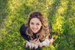 Взгляд высокого угла красивой счастливой девушки усмехаясь на камере пока стоящ на зеленой траве Стоковое Фото
