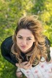 Взгляд высокого угла красивой счастливой девушки усмехаясь на камере пока стоящ на зеленой траве Стоковые Изображения