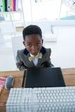 Взгляд высокого угла мальчика имитируя как бизнесмен сидя в офисе Стоковая Фотография RF