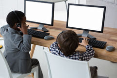 Взгляд высокого угла мужских коллег говоря через шлемофон на столе стоковое изображение