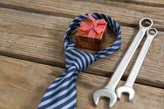 Взгляд высокого угла подарочной коробки с инструментами галстука и работы на таблице Стоковое Изображение RF