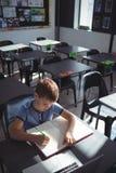 Взгляд высокого угла сочинительства мальчика в книге на столе Стоковые Изображения RF