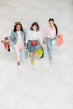 Взгляд высокого угла стильных молодых женщин идя с хозяйственными сумками Стоковые Фото