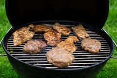Взгляд высокого угла суккулентных стейков и бургеров варя на барбекю над горячими углями на зеленой лужайке outdoors Стоковые Фотографии RF