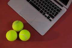 Взгляд высокого угла теннисных мячей компьтер-книжкой Стоковое Фото