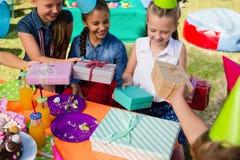 Взгляд высокого угла усмехаясь девушки получая подарки от друзей Стоковое Фото