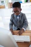 Взгляд высокого угла eyeglasses бизнесмена нося используя компьютер Стоковое Изображение