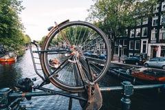 Взгляд в Амстердаме, взгляд канала через колесо велосипеда припарковал на br Стоковые Изображения RF