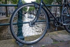 Взгляд в Амстердаме, взгляд канала через колесо велосипеда припарковал на br Стоковое Фото