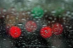 Взгляд города ночи через окно на ненастной ноче, дождевые капли падает на лобовое стекло автомобиля Жизнь концепции  Стоковые Фотографии RF