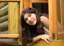 взгляд девушки из деревянного окна в загородном доме блока Стоковые Фото