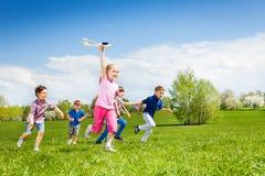 Взгляд девушки с игрушкой самолета и после за детьми Стоковая Фотография