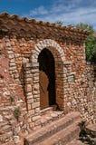 Взгляд деревянных двери и стены и свода в камне под солнечным голубым небом, в Руссильоне Стоковое фото RF