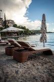 Взгляд 2 деревянных sunbeds с зонтиками на пляже моря Стоковое Изображение