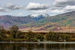 Взгляд лесистых покрашенных гор и реки осенью Стоковая Фотография