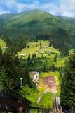 Взгляд лета landscapevillage Vorohta Украины прикарпатских гор Зеленые леса, холмы, травянистые луга и голубое небо Стоковая Фотография