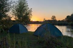 Взгляд захода солнца на спокойном реке и малых туристских шатрах Стоковая Фотография