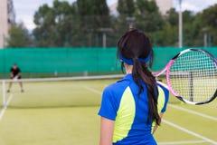 Взгляд задней стороны девушки с ракеткой тенниса на ее плече Стоковое фото RF