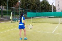 Взгляд задней стороны красивой sporty девушки играя теннис Стоковые Изображения