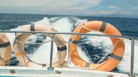 Взгляд задней части шлюпки, которая носила круг 3 спасений, быстро поворачивая голубой океан, вырезывание волны видеоматериал
